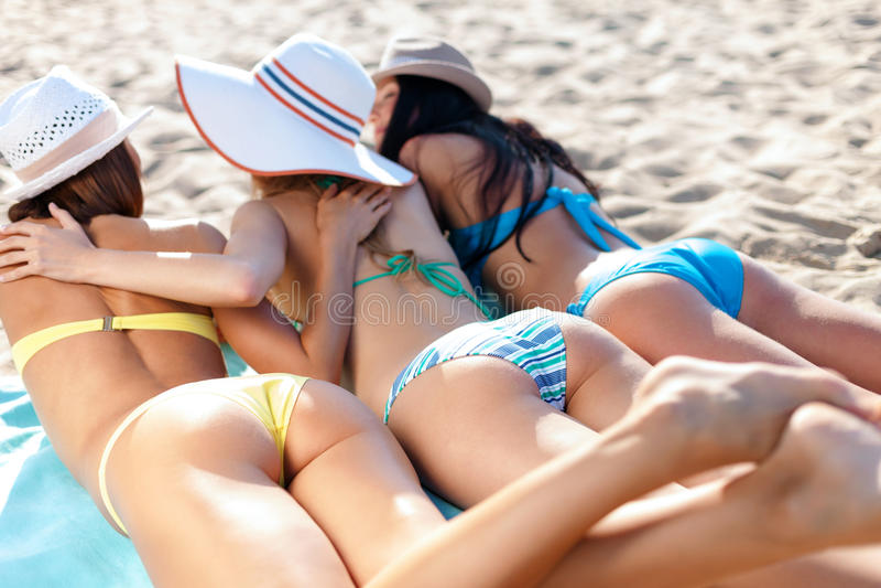 Girls sunbathing on the beach. Summer holidays and vacation - girls in bikinis sunbathing on the beach stock image