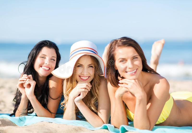 Girls sunbathing on the beach. Summer holidays and vacation - girls in bikinis sunbathing on the beach stock photo