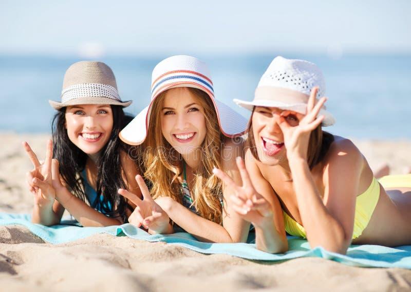 Girls sunbathing on the beach. Summer holidays and vacation - girls in bikinis sunbathing on the beach royalty free stock images
