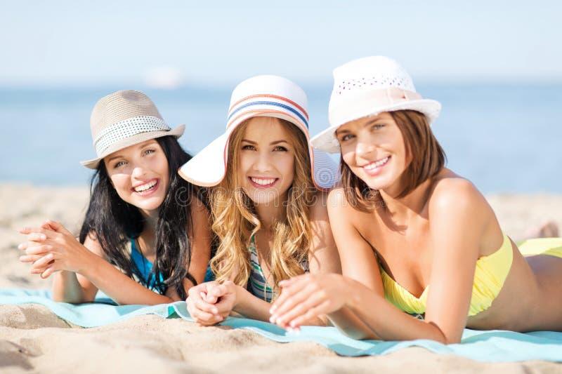 Girls sunbathing on the beach. Summer holidays and vacation - girls in bikinis sunbathing on the beach stock photos
