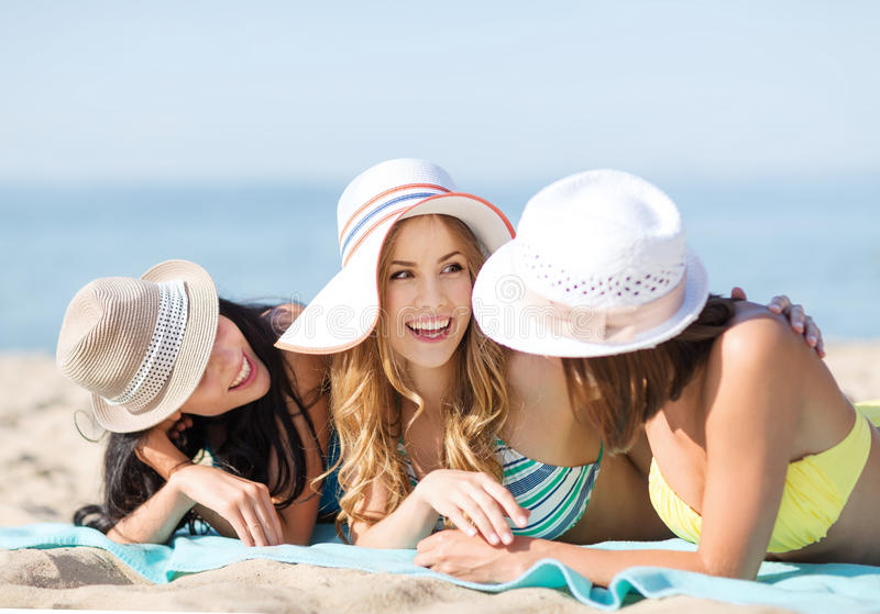 Girls sunbathing on the beach. Summer holidays and vacation - girls in bikinis sunbathing on the beach royalty free stock photo