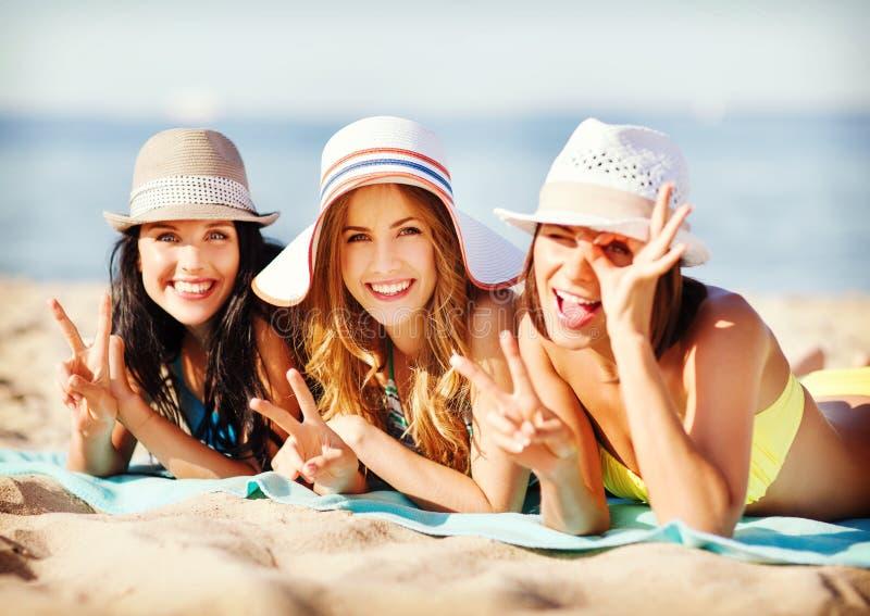 Girls sunbathing on the beach. Summer holidays and vacation - girls in bikinis sunbathing on the beach royalty free stock photos