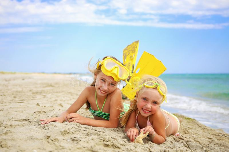 Girls sunbathing in mask and fins for scuba diving. Girls sunbathing on beach in mask and fins for scuba diving stock image