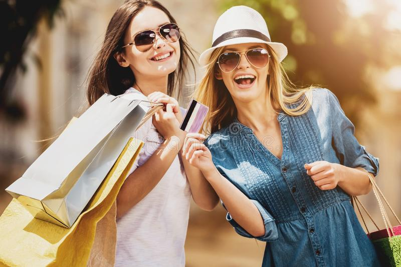 Girls in Sunglasses with Credit Card in Their Hand. Laughing into Camera. Reducing Stress by Buying. Good Time. Cute Friends in Sunglasses Holding Shopping Bags royalty free stock photos
