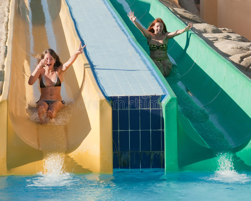 Girls in swimming pool water slide royalty free stock images