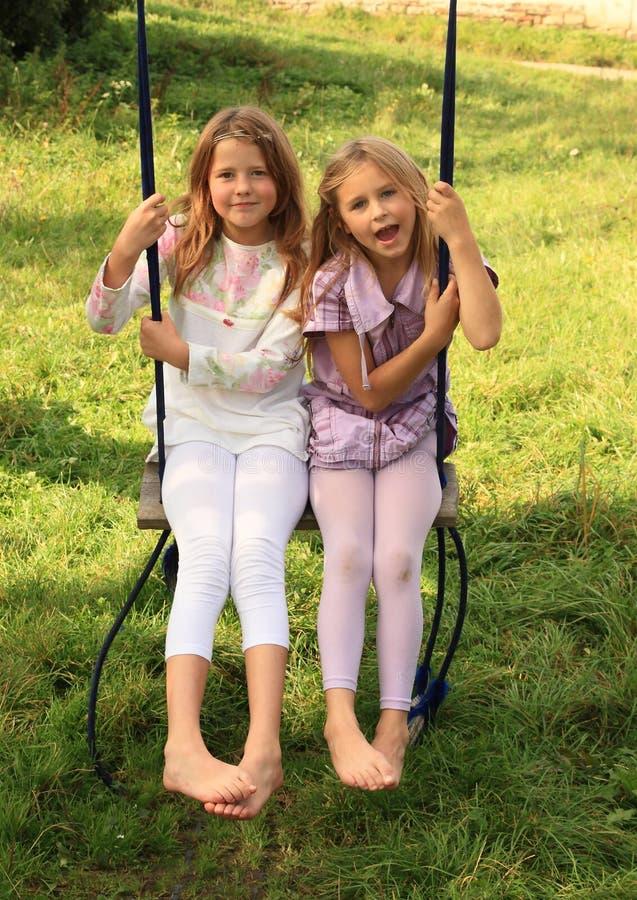 Girls swinging on swing royalty free stock photo