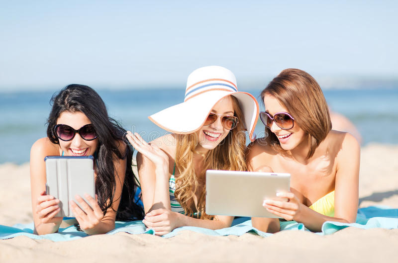 Girls with tablet pc on the beach royalty free stock image