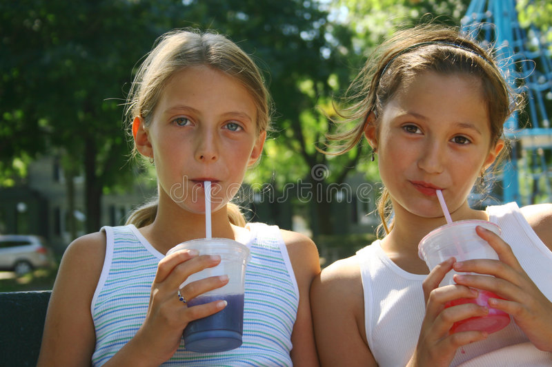 Girls With Takeout Drinks. Two preteen girls drinking from takeout cups with straws. Taken outdoors royalty free stock images