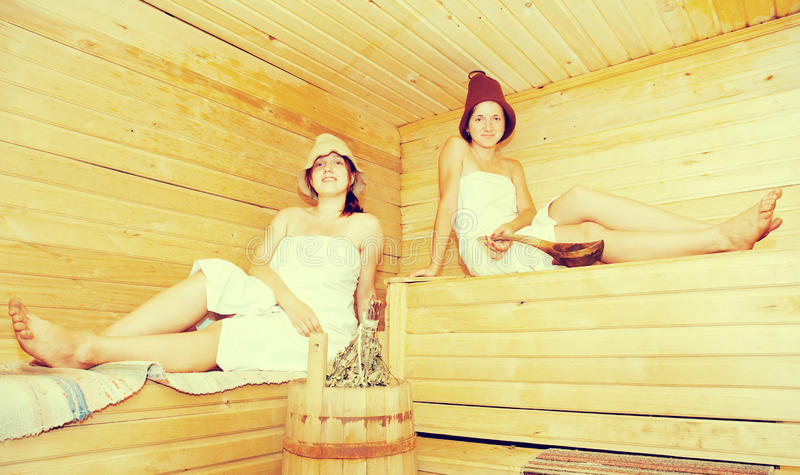 Girls is taking steam-bath. Young women sits on bench in sauna stock image