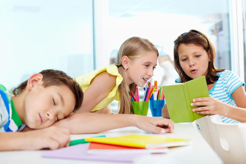 Girls talk. Cute schoolgirl showing her classmate her notes, tired boy napping on desk near by stock photography