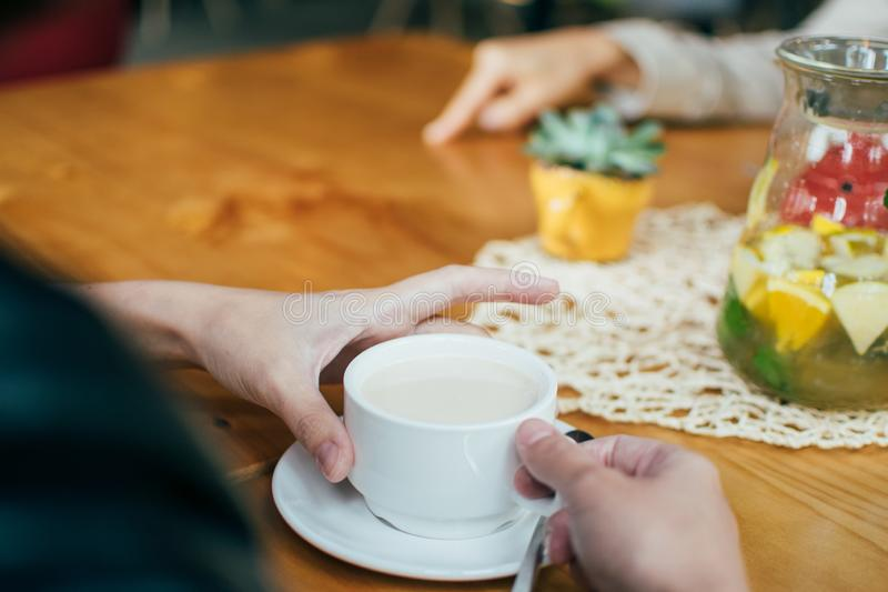 Girls talking in cafe and drinking coffee, meeting friends in summertime together, at wooden table, background royalty free stock images