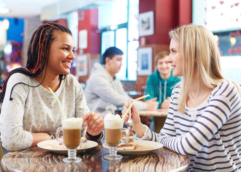 Girls talking. Image of two teenage girls eating cakes and talking in cafe royalty free stock images