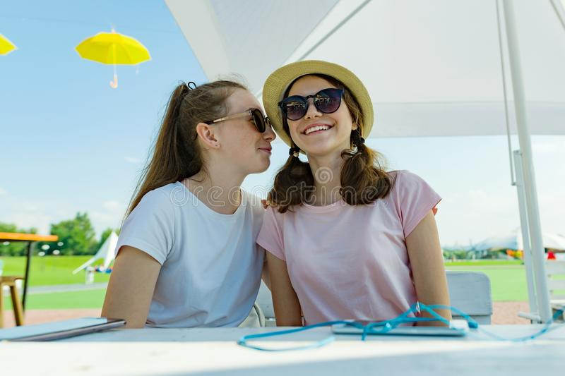 Girls teenagers having fun, talk, secret, laugh. Sit in a street cafe, sunny summer day in recreation and entertainment area. royalty free stock photo
