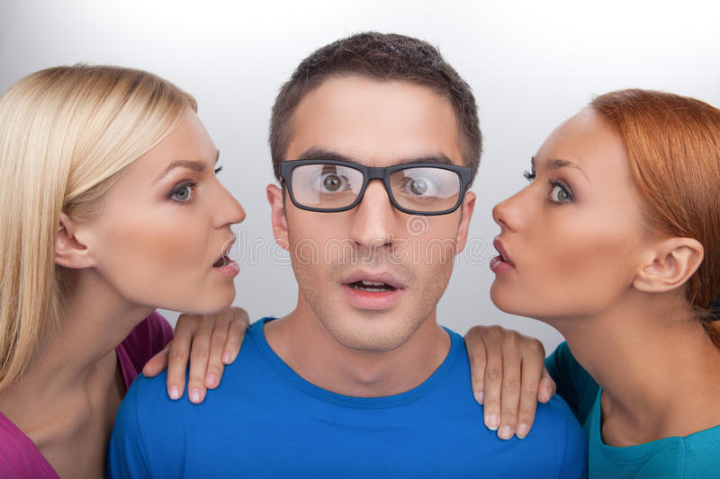 Girls telling gossips. Two beautiful young women telling gissips to the men in eyeglasses while standing isolated on gray royalty free stock photo