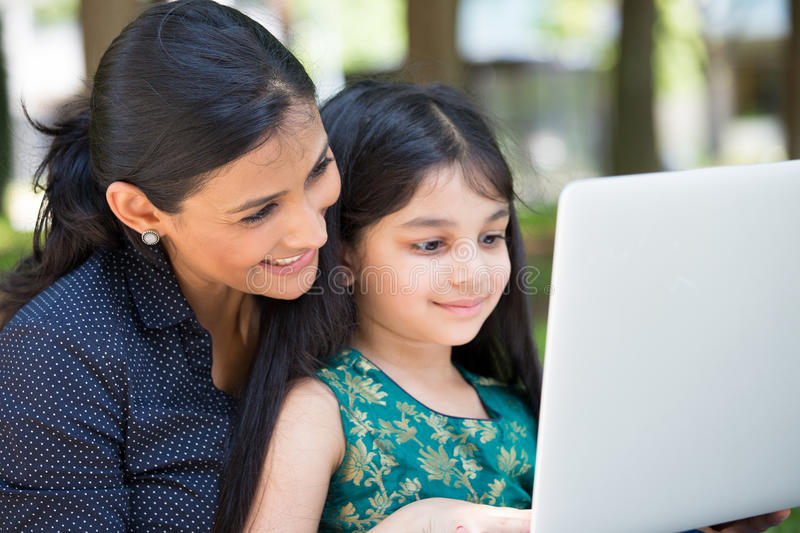 Girls and their laptop. Closeup portrait, family looking at silver laptop together, outdoors outside background stock photo