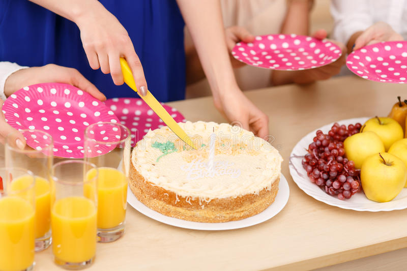 Girls are about to share a birthday cake. Cutting the cake. Close up of girls cutting and sharing birthday cake stock image