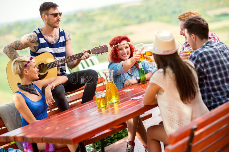 Girls toast with glasses of beer while tattooed boy play guitar. Two young girls with glasses of beer toasts while tattooed boy play guitar on in nature stock photo