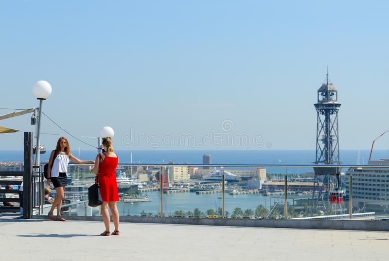Girls - tourists are photographed on viewing platform on mountain Montjuic against backdrop of port of Barcelona, Spain stock photos