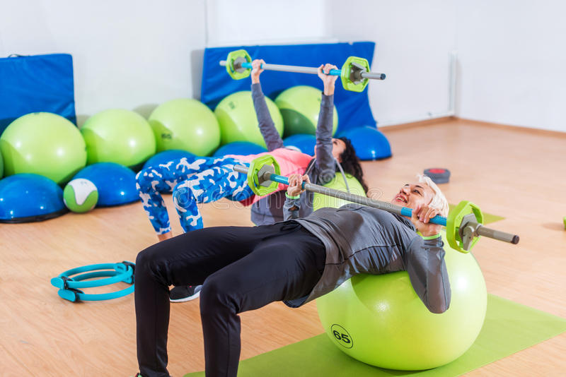 Girls in tracksuits lying on fitness balls doing barbell chest press in a gym. Two young women exercising indoors. stock photos