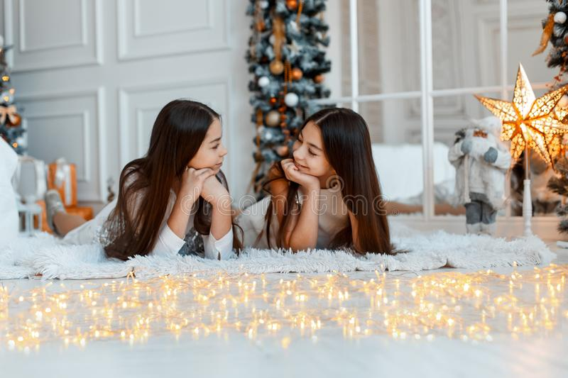 Girls twins in front of the fir-tree. New year`s eve. Christmas. Cozy holiday at the fir-tree with lights royalty free stock photo