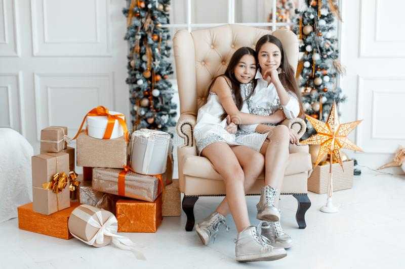 Girls twins in front of the fir-tree. New year`s eve. Christmas. Cozy holiday at the fir-tree with lights royalty free stock photography