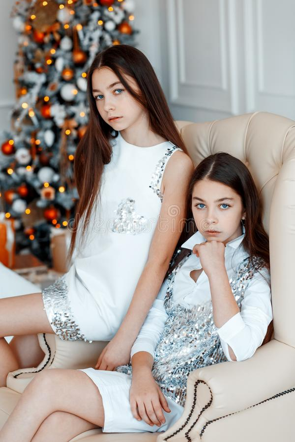 Girls twins in front of the fir-tree. New year`s eve. Christmas. Cozy holiday at the fir-tree with lights stock images