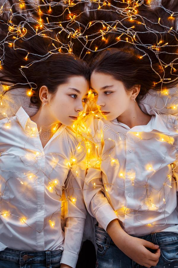 Girls twins with lights. New year`s eve. Christmas. Cozy holiday at the fir-tree with lights and gold decor stock photos