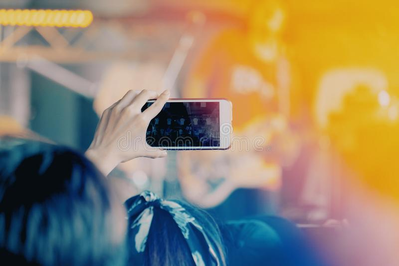 Girls use smartphones to take pictures at concerts. Holding, camera, cell, hand, woman, mobile, photo, person, background, technology, people, travel, light royalty free stock image