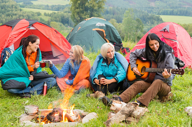 Beside campfire girls sitting listening to guitar. Girls on vacation camping with tents listening girl playing guitar royalty free stock photos