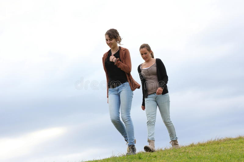Girls walking down a grassy hill stock photography