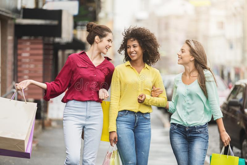Girls walking along city street after shopping royalty free stock photo