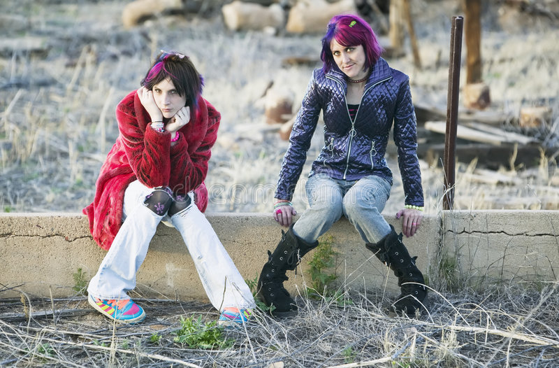 Girls on a Wall. Two Fashion Girls Sitting on a Cement wall stock image