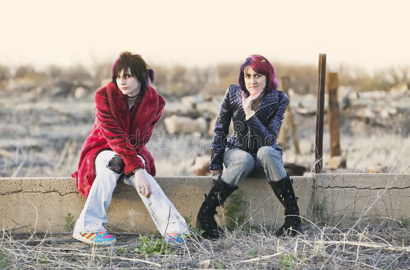 Girls on a Wall. Two Fashion Girls Sitting on a Cement wall royalty free stock photography