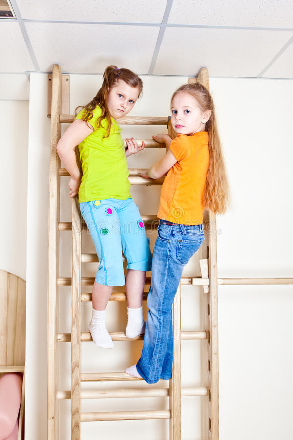 Girls on wall bars. Two girls on the wooden wall bars stock photo