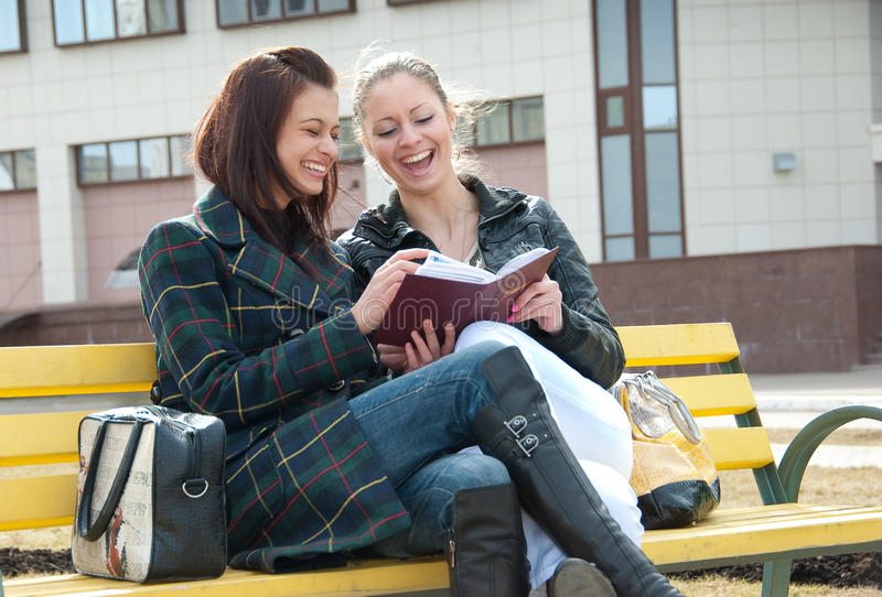 Girls watching photos in album. Two happy girls watch photos in album sitting on a bench outdoors stock photography