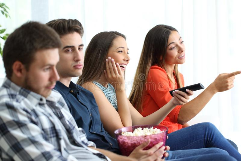Girls watching romantic movie with their bored boyfriends royalty free stock image