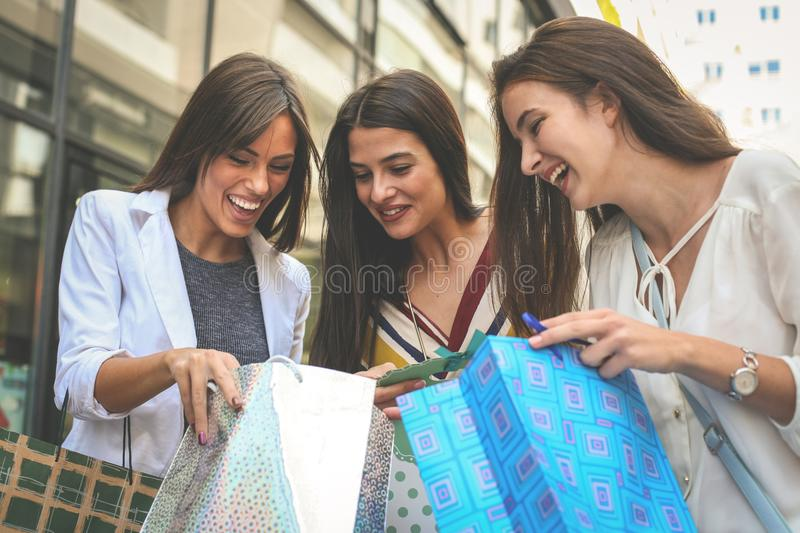 Girls watching their new clothes. Tree best friend enjoying in. Spring day.Lifestyle royalty free stock photography