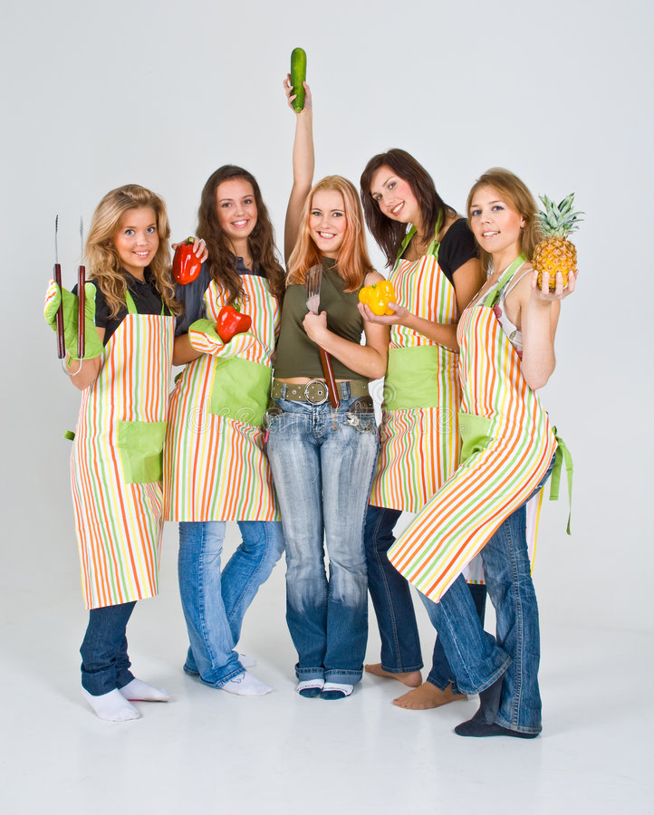 Girls Wearing Aprons. Group of girls wearing colorful striped aprons hold fruits and vegetables royalty free stock photo