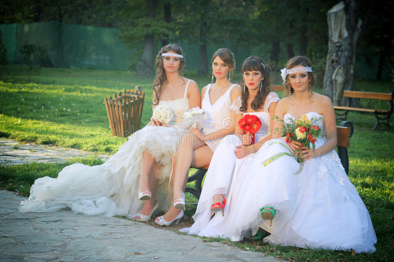 Girls in a wedding dresses. Sitting on a park bench stock photos