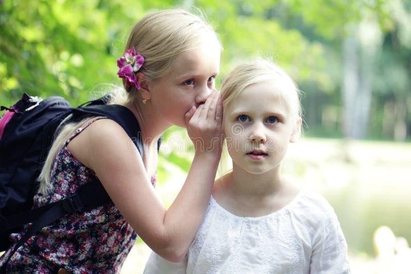 Girls Whisper In för två syster öra utomhus Begrepp av skämtet, hemlighet, fantasi, konversation, viskning överrrakning Sinnesrör royaltyfria bilder