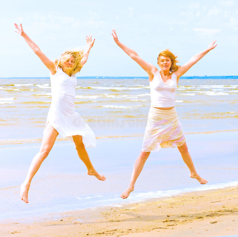 Girls in white jumping happily on a beach stock photography