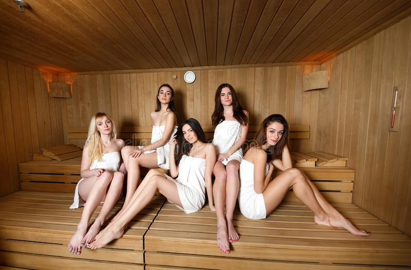 Girls in white towels relaxing in the sauna. stock image