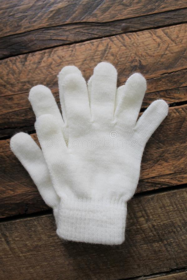 Girls White Winter Gloves Isolated on Wooden Background royalty free stock photography
