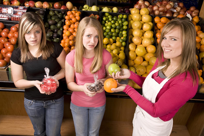 Girls yuck. Two teen girls not wanting to take the orange from the worker, they would rather have the candy royalty free stock photos