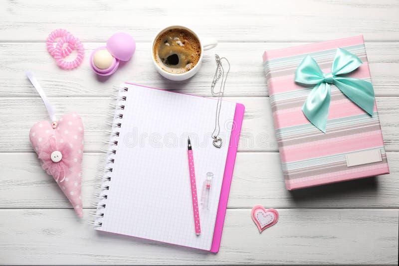 Girly аксессуары с тетрадью, чашкой кофе и подарочной коробкой на w стоковые изображения rf