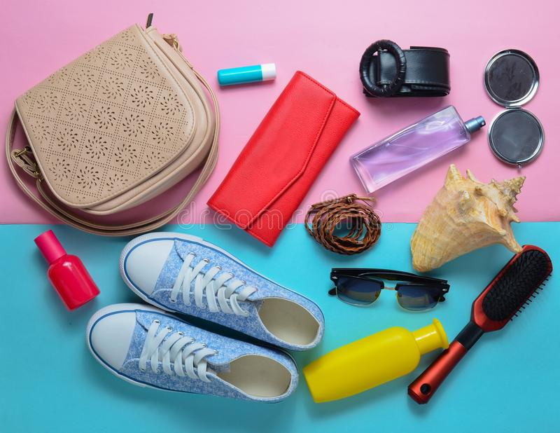 Girly fashionable spring and summer accessories: sneakers, cosmetics, beauty and hygiene products. A bag, sunglasses on a pink blue pastel background. What&# royalty free stock images
