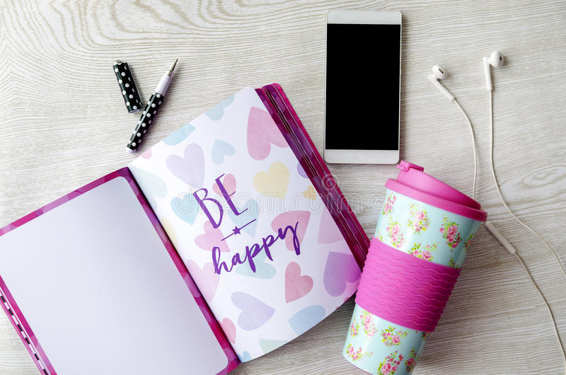 Girly thermos, notebook, phone and headphones on white wooden table. Flatlay royalty free stock photography