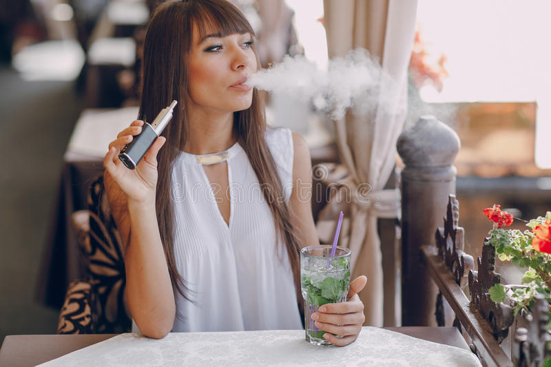 Girn in cafe with E-Cigarette. Beautiful brunette smoke electronic cigarette on the summer terrace of restaurant royalty free stock photo