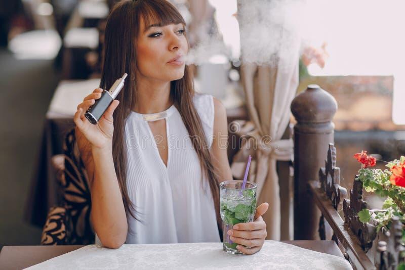 Girn no café com E-cigarro fotografia de stock royalty free