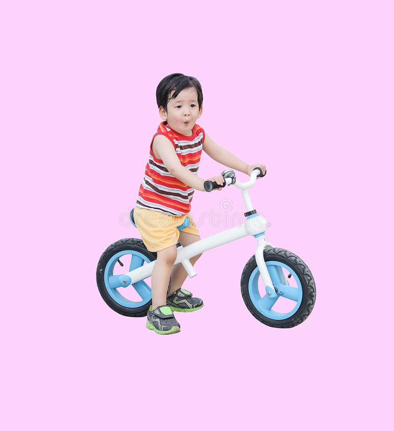 Giro asiatico sveglio del bambino del primo piano una bicicletta nell'umore emozionante isolata su fondo rosa fotografia stock